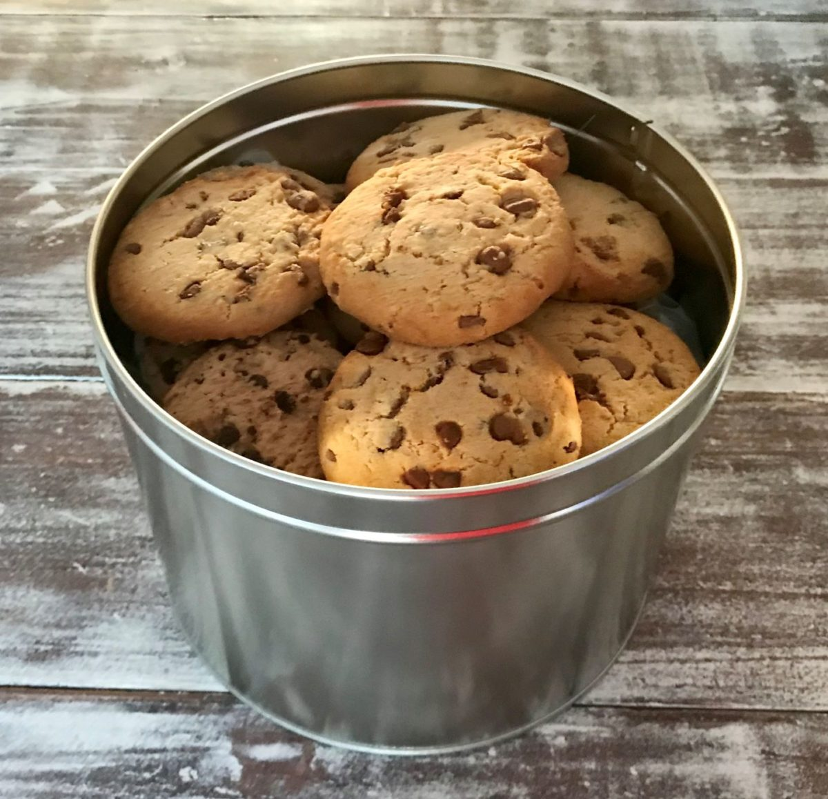 Chocolate chip cookies in a giant silver tin